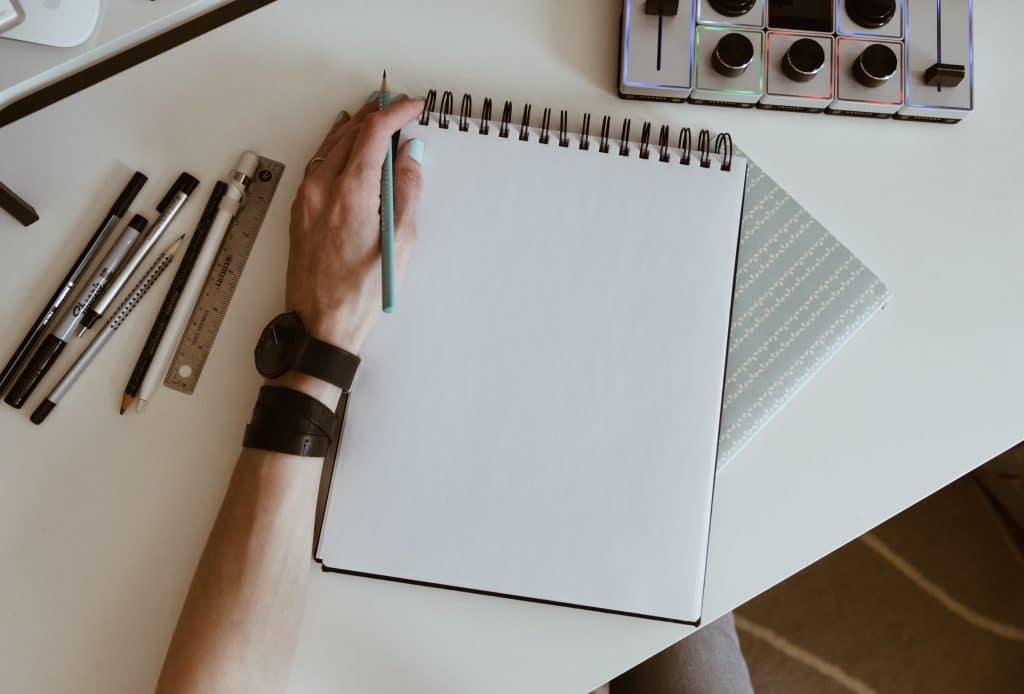 Mesa com mão apoiada e caderno e canetas vistas de cima