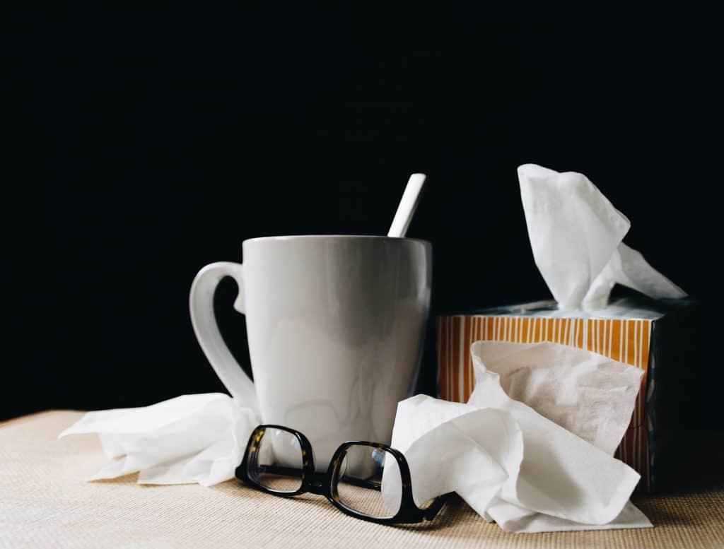 Mesa com um óculos, xícara e uma caixa de lenços