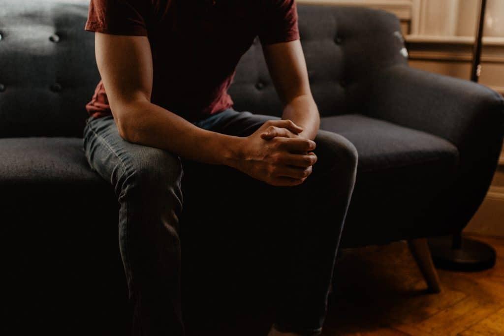 Homem sentado no sofá, com as mãos unidas e os braços apoiados nas pernas.