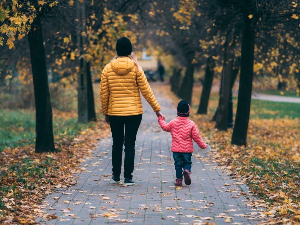 Mãe e filho de mãos dadas caminhando em caminho de parque com folhas de outono caindo