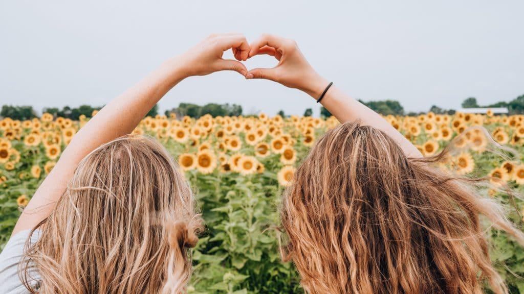 Duas garotas formando um coração com as mãos.