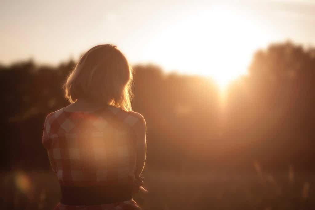 Mulher olhando para as árvores e para o sol