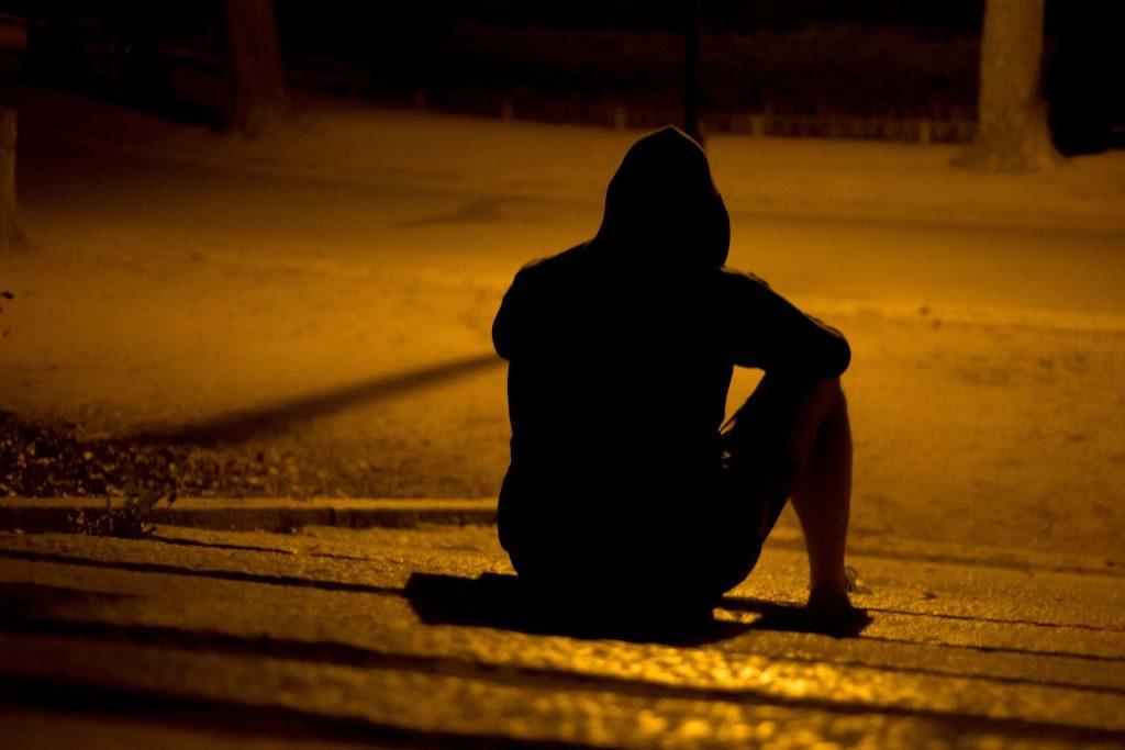 Imagem de um  homem sentado na guia de uma calçada. Ele veste uma roupa preta e usa uma touca da blusa sobre a sua cabeça.