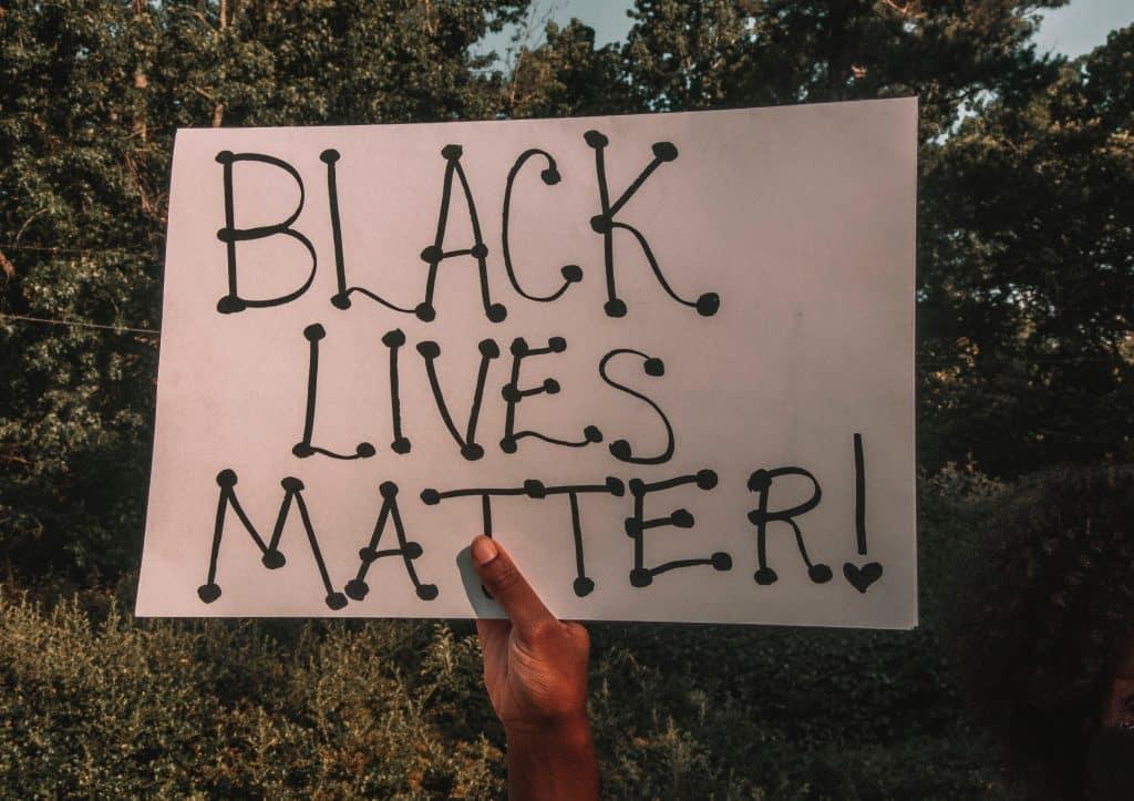 """Pessoa segurando cartaz escrito """"vidas negas importam"""" em inglês"""