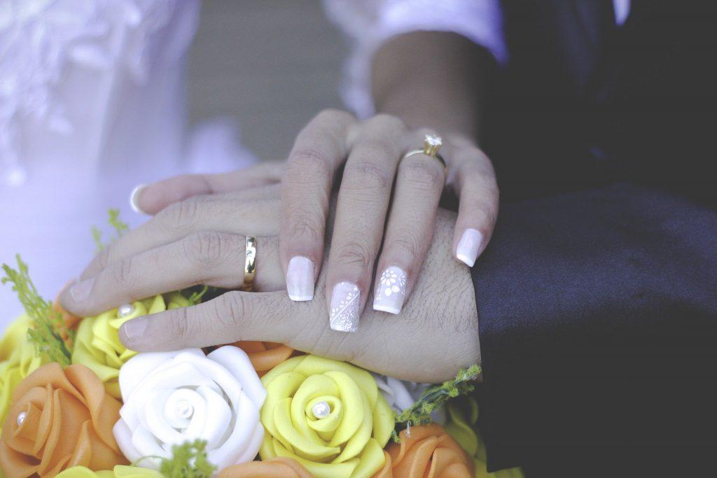 Imagem das mãos de um casal de homem e mulher usando alianças na cerimônia de casamento, As mãos estão posicionadas sobre o buquê de noiva feito de flores amarelas, brancas e alaranjadas.