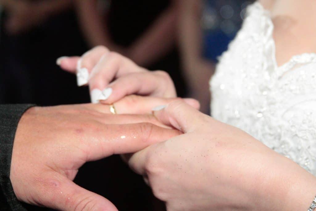 Mulher colocando aliança no dedo da mão esquerda doo seu esposo em uma cerimônia de casamento.