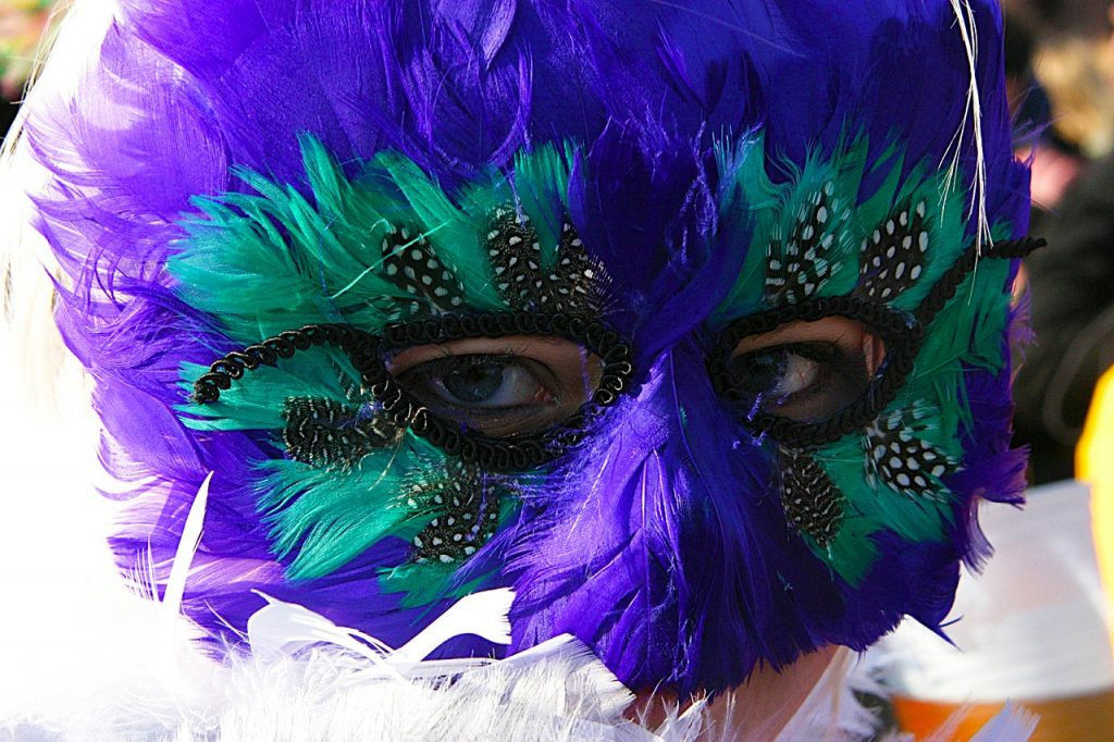 Mulher usando máscara de rosto inteiro, coberta com penas roxas e verdes. Apenas seus olhos não estão cobertos.