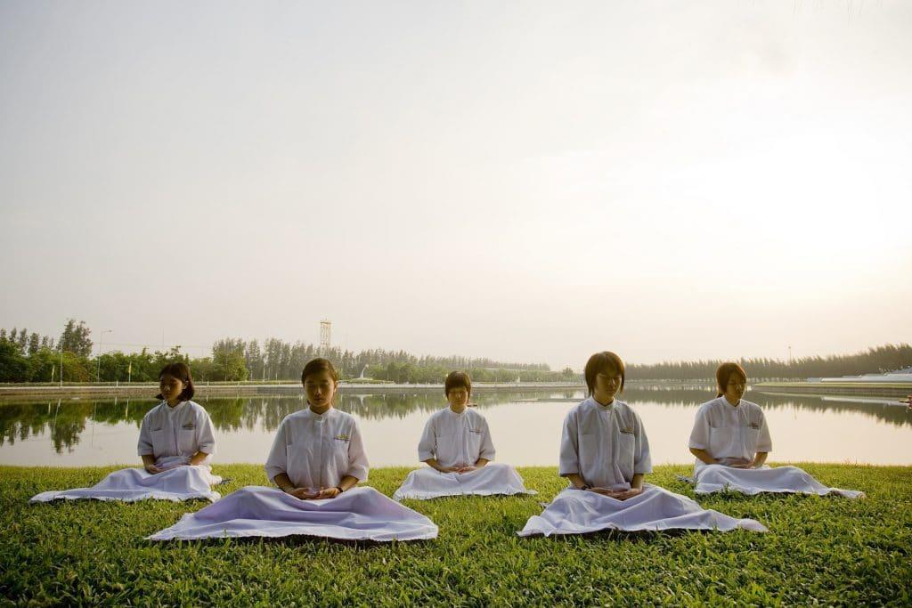 Imagem de um grupo de crianças japonesas meditando em uma escola. São cinco crianças sentadas em um gramado verdinho, todas vestindo roupas brancas.