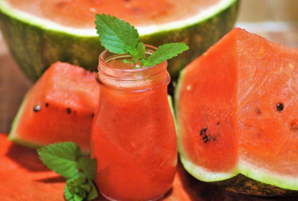 Suco de melancia servido em uma jarra de vidro decorado com hortelã. Ao lado melancias cortadas ao meio.
