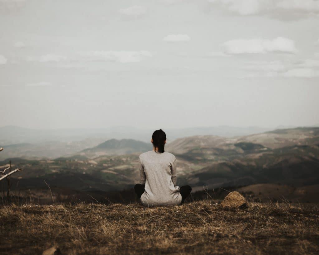 Mulher sentada no chão, de costas, no topo de um morro. Com uma camiseta e os cabelos presos, ela admira a paisagem montanhosa ao fundo, em um dia nublado.