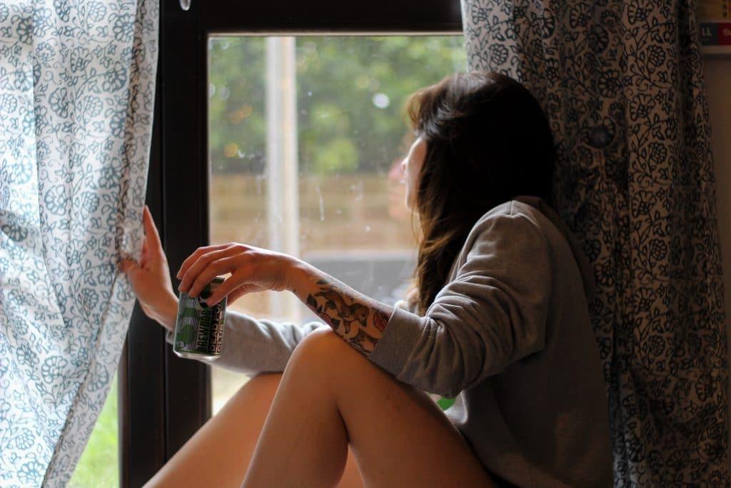 Mulher na janela com latinha de bebida na não