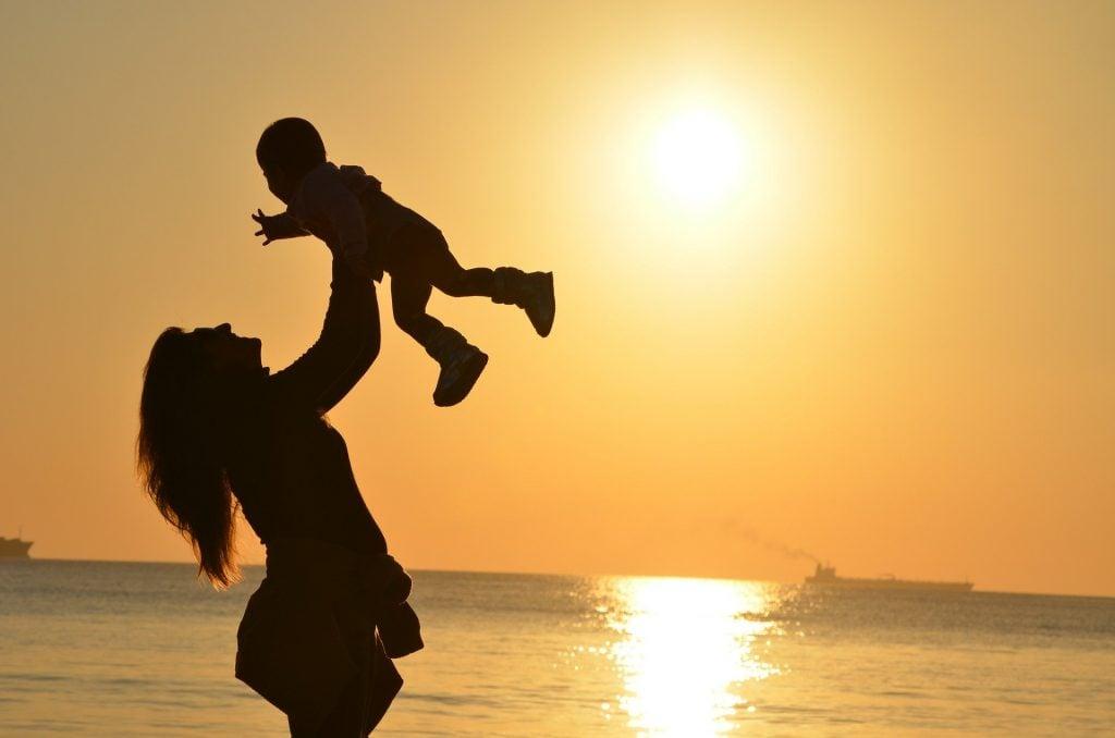 Imagem de uma mãe segurando e levantando o seu filho no colo. Ao fundo a luz brilhante de um lindo por do sol.
