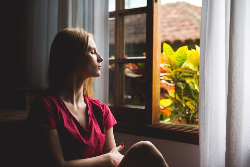 Mulher sentada em frente à janela, de olhos fechados, meditando.