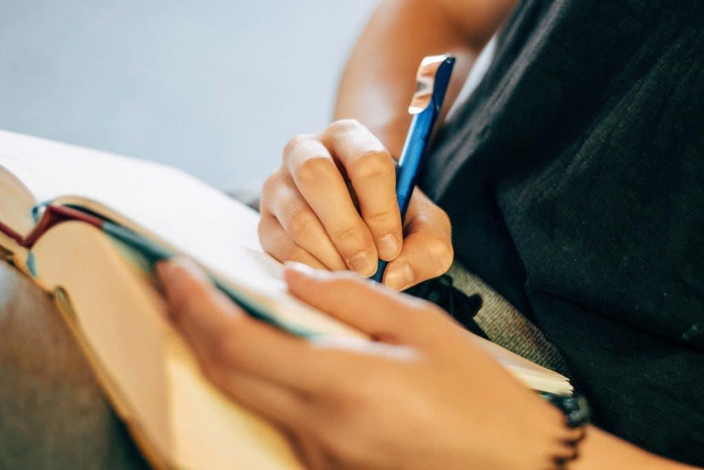 Pessoa escrevendo em um caderno com uma caneta.