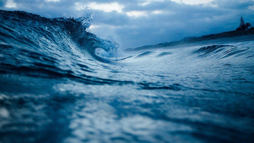 Imagem de um oceano bem azul com uma onda quebrando no começo do mar.