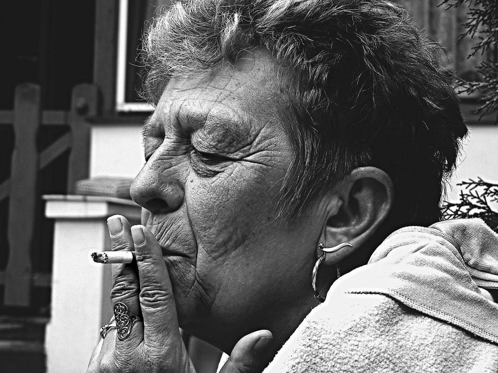Imagem de uma senhora fumando. Ela está bem envelhecida. Tem cabelo curto, usa anel e brincos de prata.