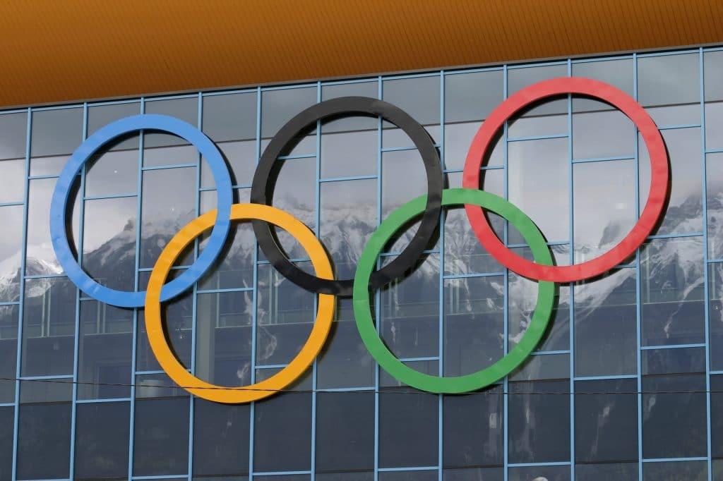 Imagem dos anéis olímpicos nas cores preto, azul, vermelho, verde e amarelo. Eles estão fixados em uma parede espelhada.