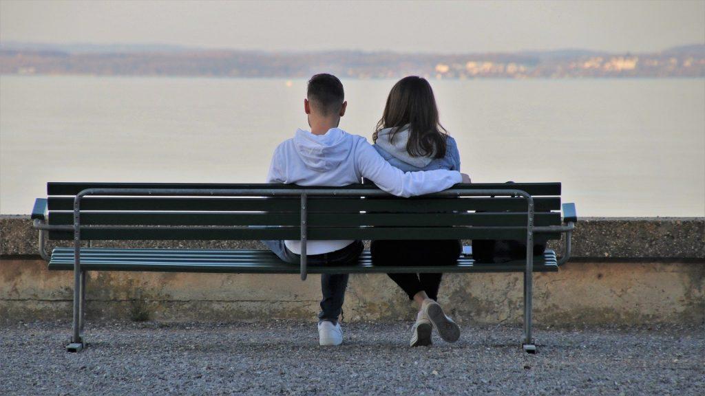 Imagem de um casal de jovens menino e menina sentados em um banco em frente a um lindo lago. Eles estão abraçados e observado a paisagem em silêncio.
