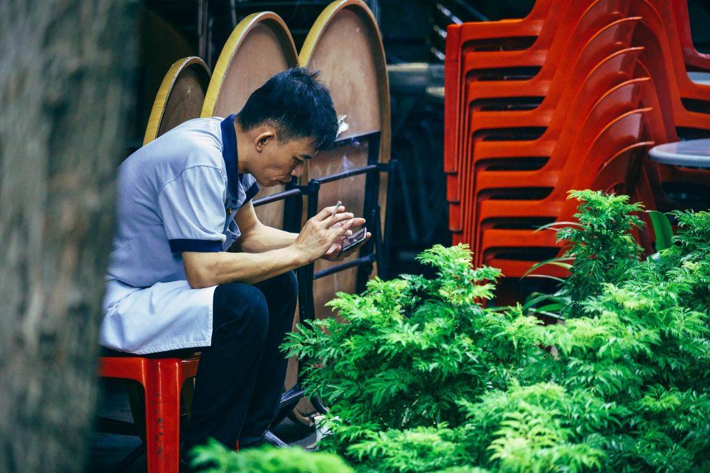 Imagem de um homem oriental sentado em uma cadeira vermelha. Ele está mexendo no celular e na outra mão segurando um cigarro aceso.
