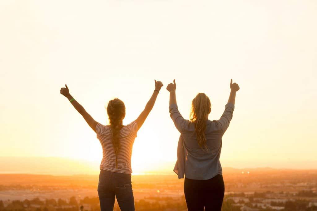 Imagem de duas mulheres de costas com os braços erguidos em sinal de positividade olhando para o por do sol.