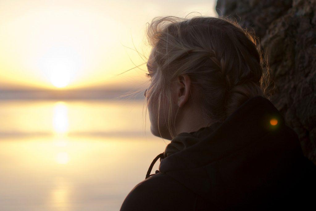Imagem de uma garota usando tranças. Ela está encostada em um árvore olhando para o por do sol em frente ao mar.
