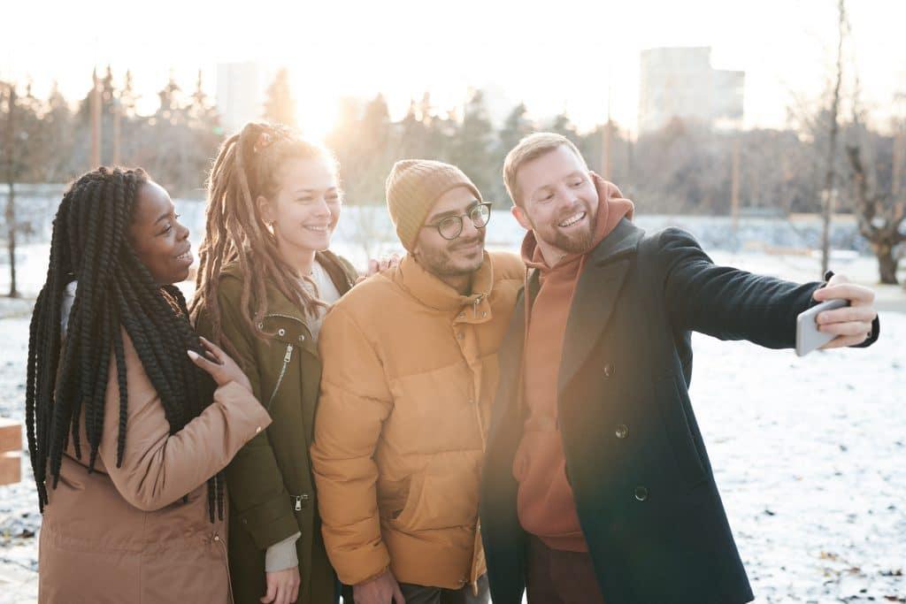 Quarteto de amigos fazendo selfie felizes