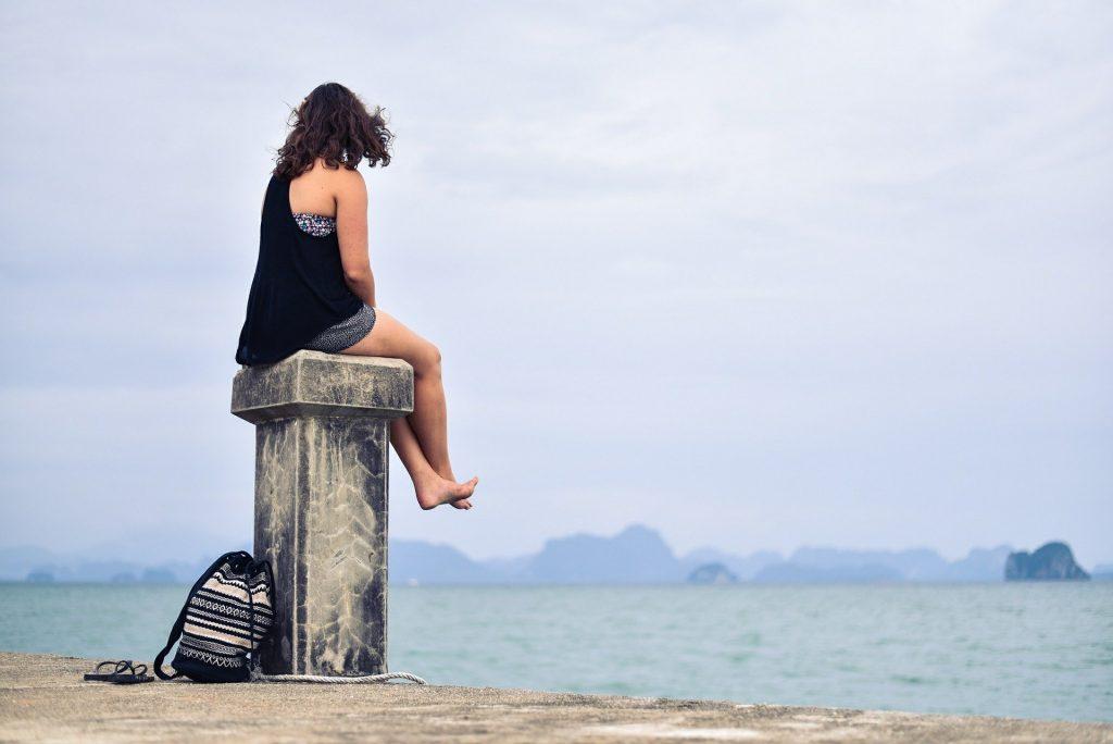 Imagem de uma mulher sozinha e em silêncio sentada sobre uma mureta em frente ao mar. Ela está concentrada e pensativa admirando a vista silenciosamente.