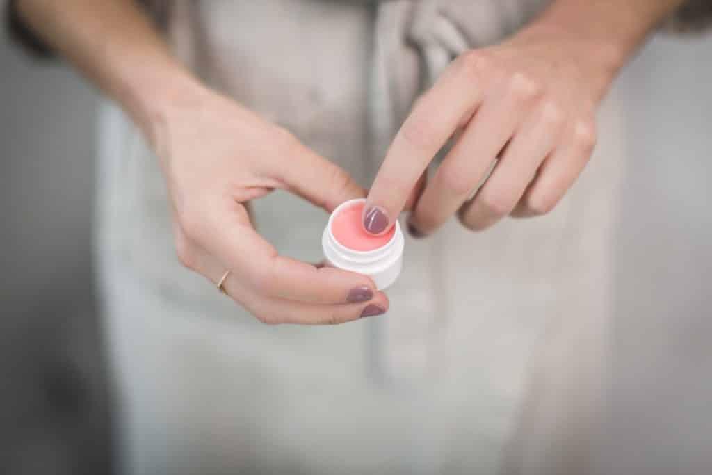 Recorte de uma mulher usando produto para cuidar da pele.