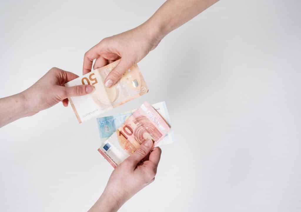 Duas pessoas trocando notas de dinheiro