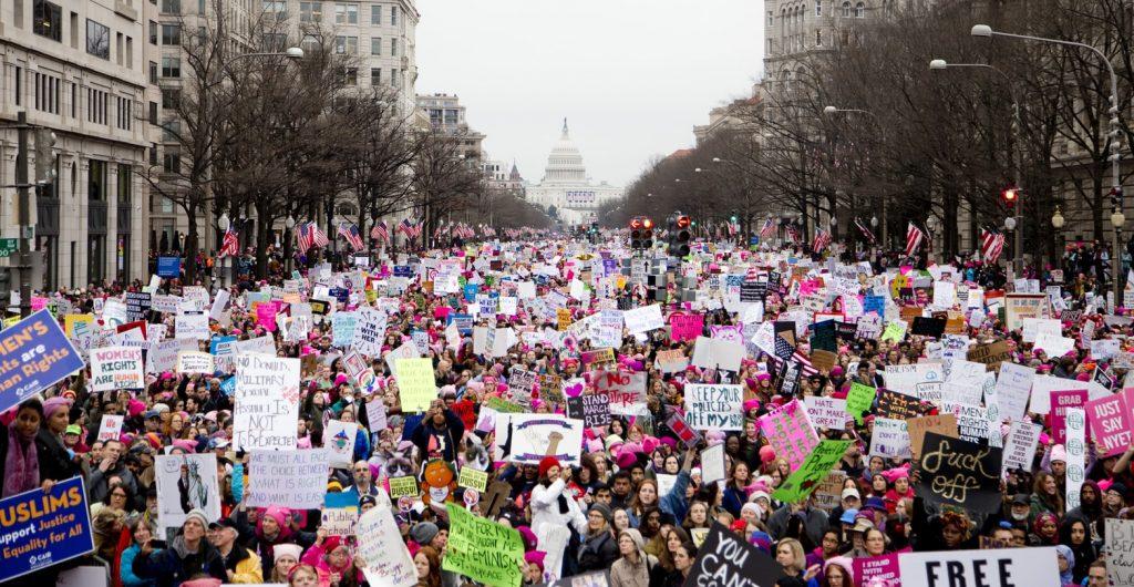 Milhares de mulheres em protesto, segurando vários cartazes coloridos exigindo direitos.
