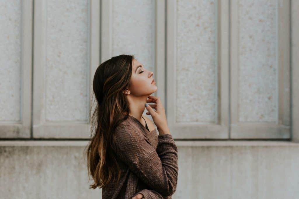 Mulher de cabelos lisos e suéter de lã vista de perfil, com os braços cruzados e a mão no pescoço, de olhos fechados.