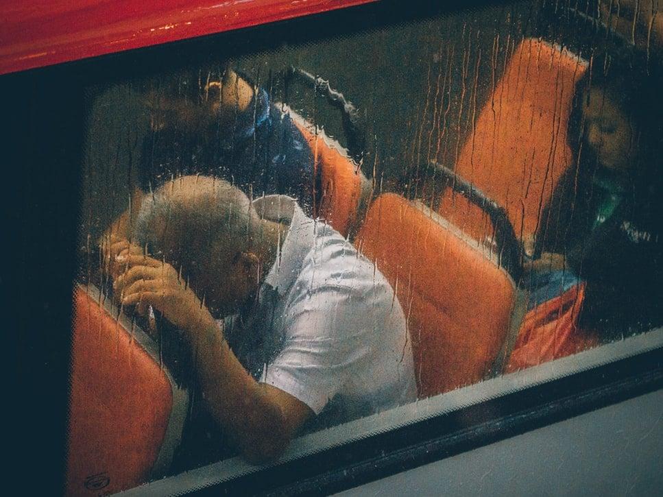 Senhor com camiseta polo branca dentro de ônibus em dia chuvoso. Ele está sentando e apoia suas mãos e sua cabeça no encosto do banco em sua frente.