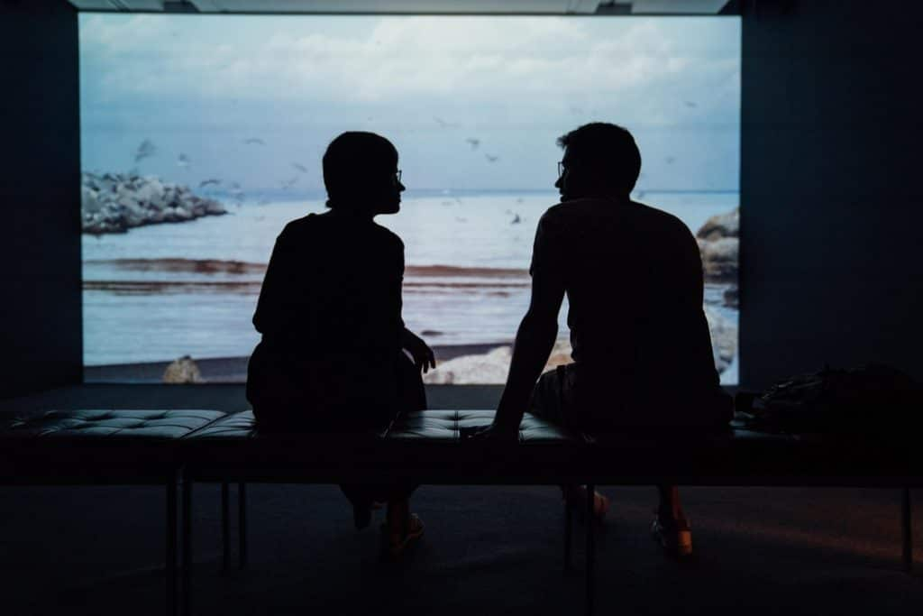 Silhueta de duas pessoas sentadas em frente a uma tela de projeção, viradas uma para a outra, conversando. Ao fundo, uma paisagem de praia é projetada na parede.