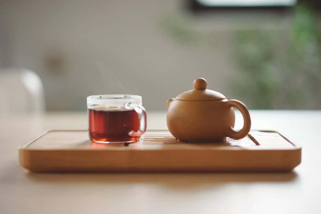 Xícara de chá quente ao lado de um pequeno bule de cerâmica.