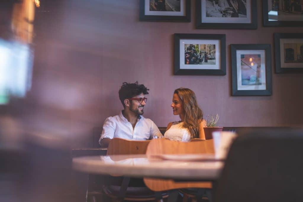 Casal de homem e mulher sentados em um restaurante, conversando e rindo.
