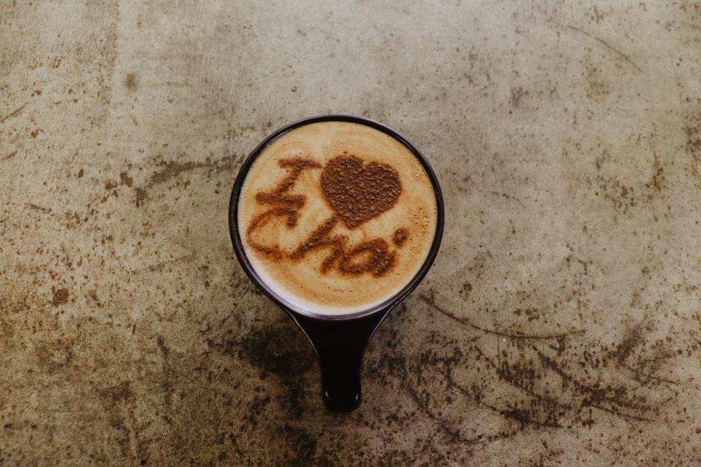 """Xícara de chá chai com os dizeres """"eu amo chai"""" escritos com canela."""