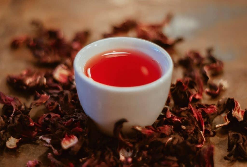 Xícara com chá de flores cercada apor flores de lavanda desidratadas.
