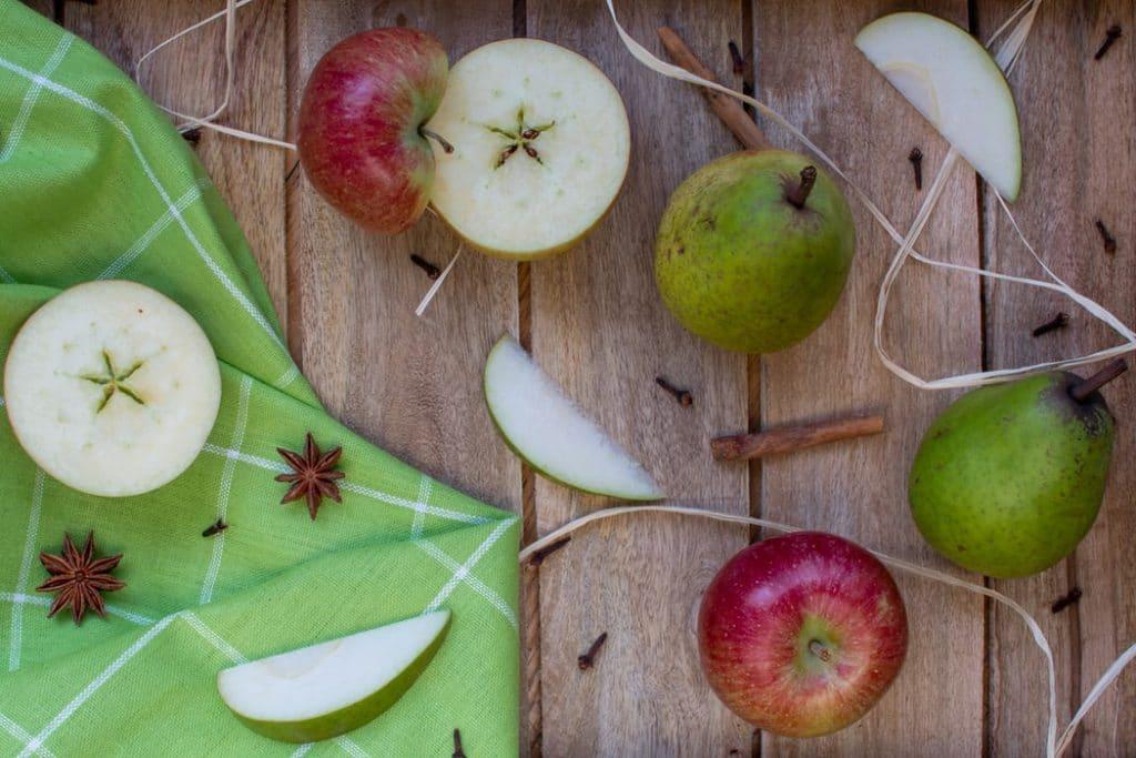Maçãs, peras e canela dispostos sobre uma mesa de madeira.