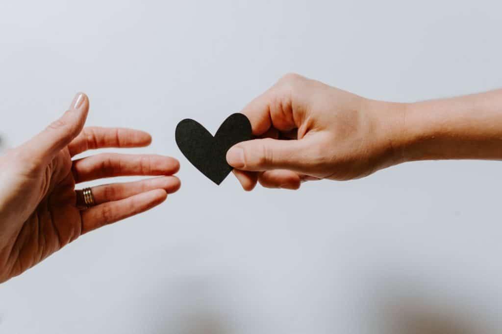 Mão de uma pessoa entregando um coração de papel à outra.
