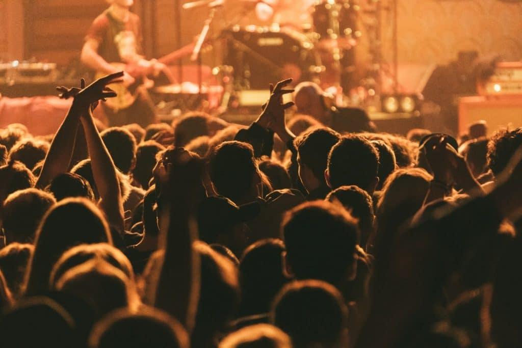 Silhueta de uma multidão de pessoas em um show de rock, com a banda tocando ao fundo.