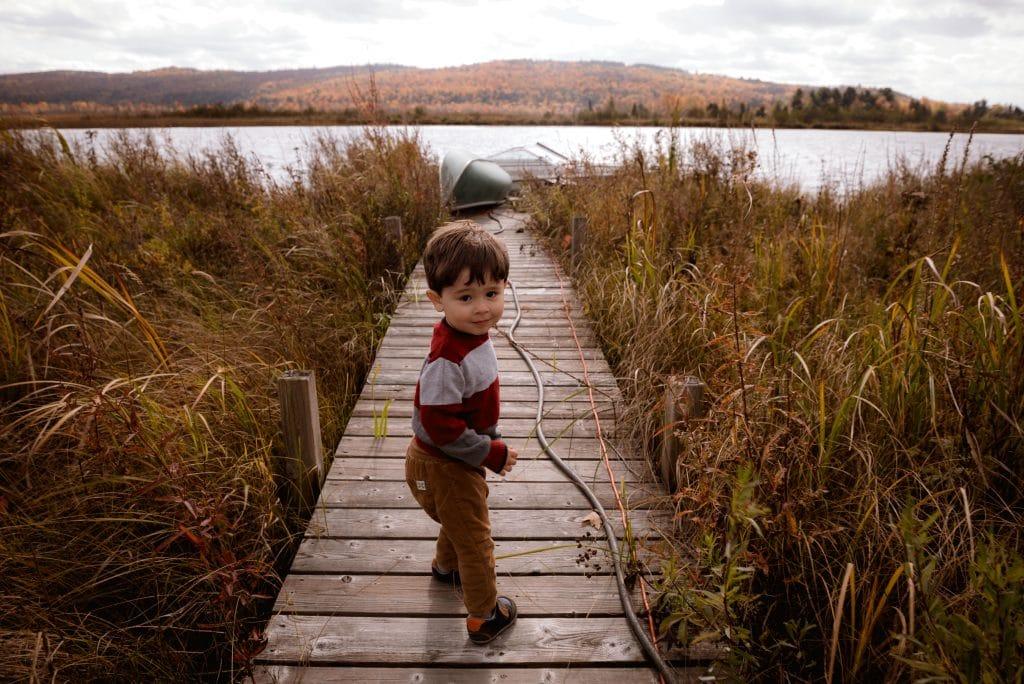 Bebê em pé em ponte com mato dos lados e lago ao fundo