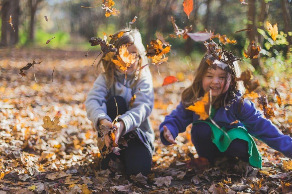 Duas meninas pequenas na natureza, brincando de jogar folhas secas para o alto.