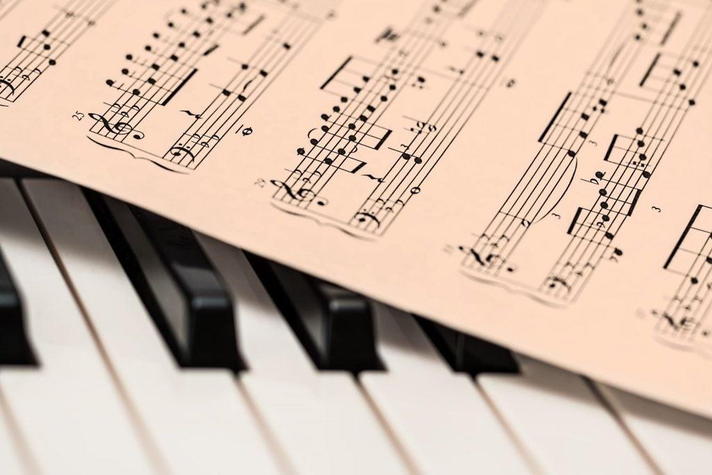Imagem de uma partitura disposta sobre o teclado de um piano.