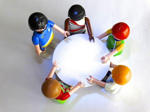 Bonecos de playmobil em volta de mesa em reunião