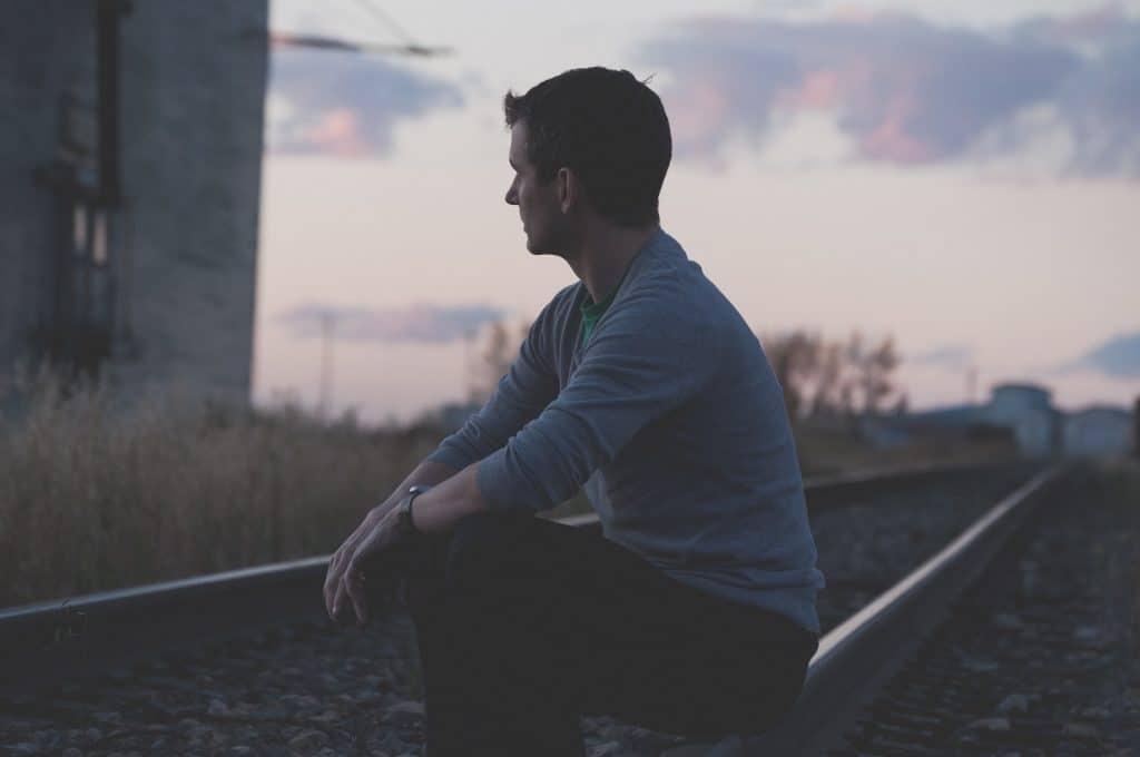 Homem sentado em trilho do trem pensativo