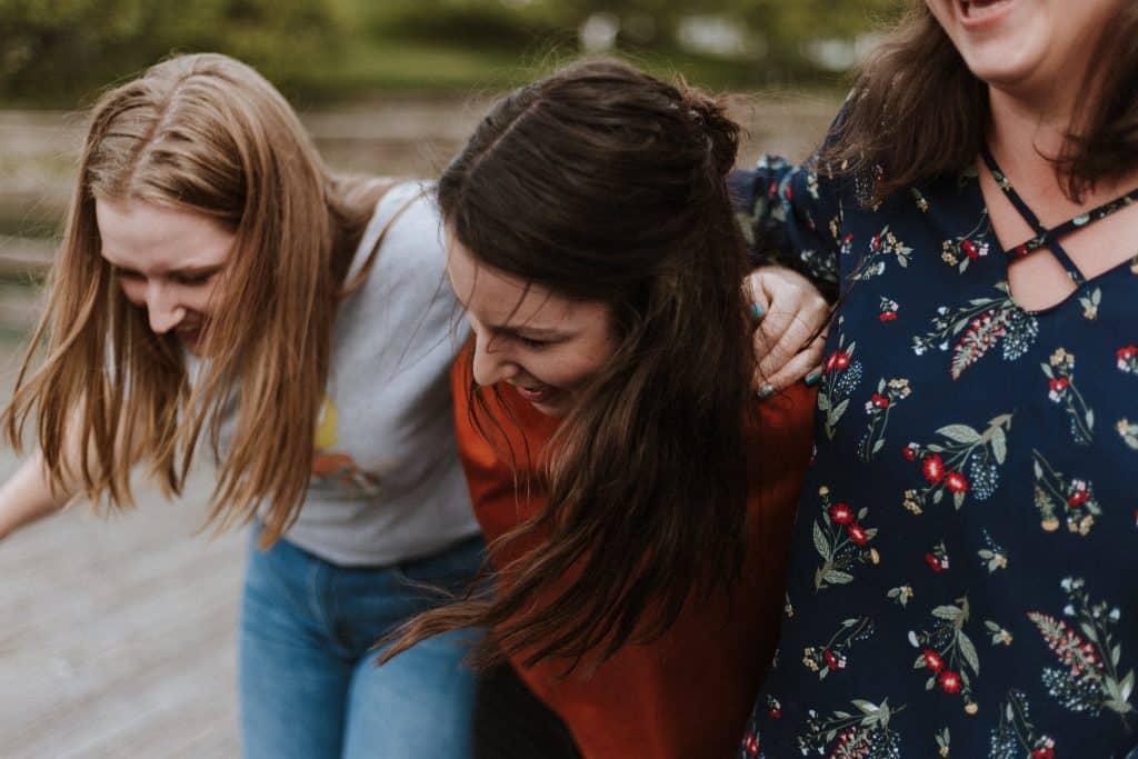 Três mulheres abraçadas e sorrindo na rua