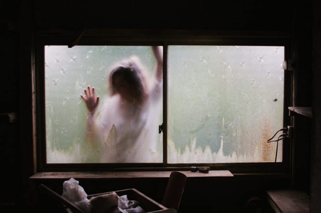 Mulher atrás de janela abafada.