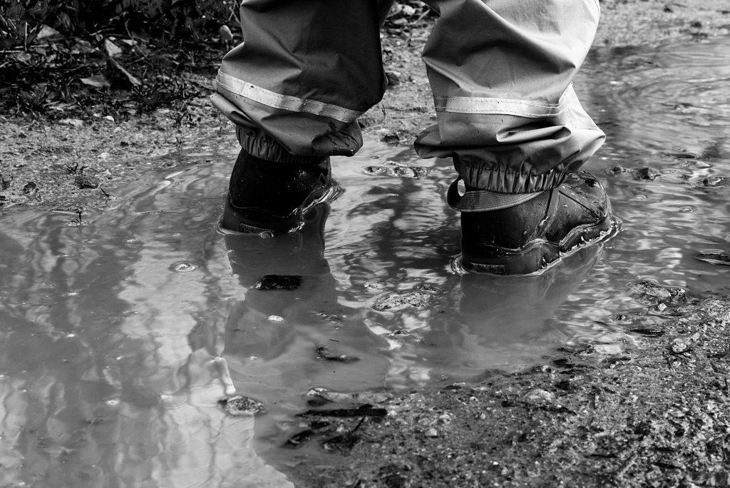 Pés de uma criança com botas sobre uma poça de água suja da chuva.