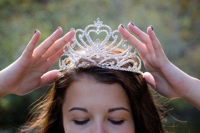 Meio rosto de mulher com coroa de princesa na cabeça e olhos fechados