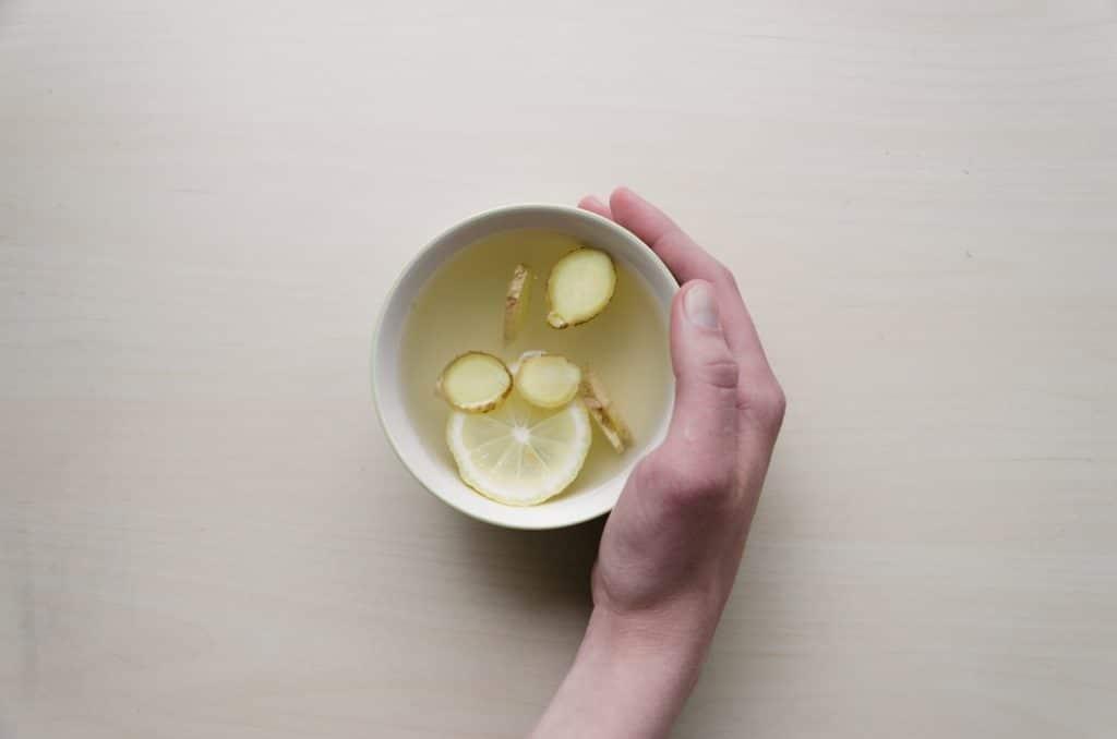 Pessoa segurando uma xícara de chá de gengibre com limão.